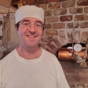 Les Saidel in front of his home made brick oven